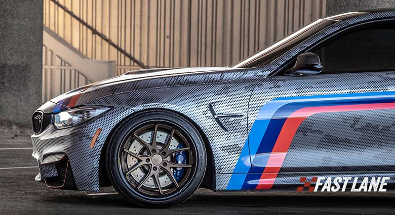 Wrapped BMW m4 with vinyl BMW decal stripes in red, royal blue, and navy blue.