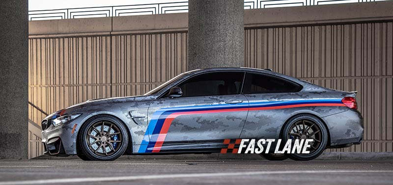 BMW M4 with vinyl wrap, decals, and printed design.