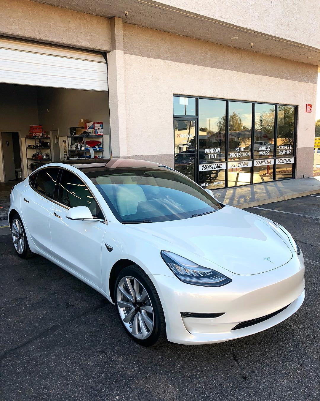 Another white Tesla in front of Fast Lane