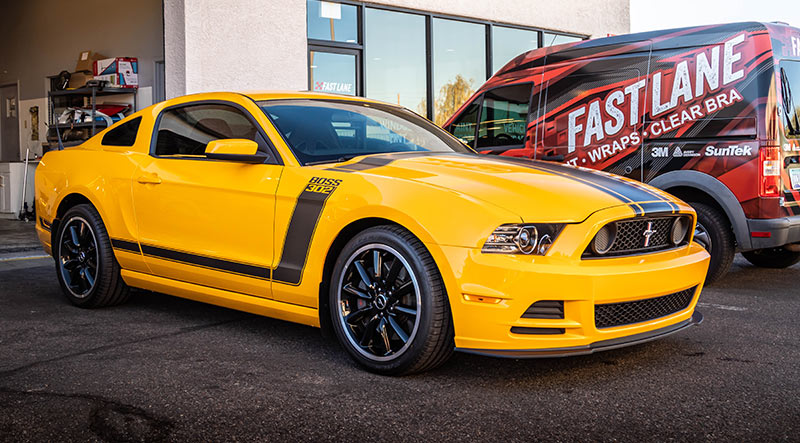Yellow mustang with stripes and tint at Fast Lane