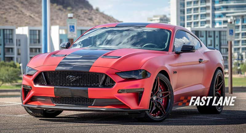 Red vinyl wrapped Mustang with black glossy stripe.